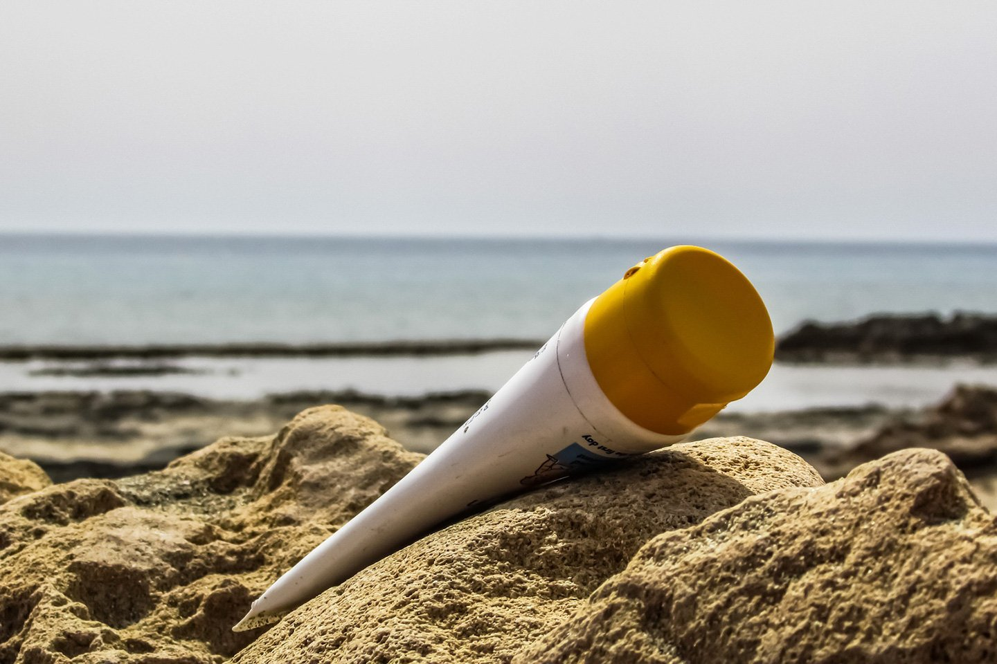 Sunscreen bottle in the sand at the beach