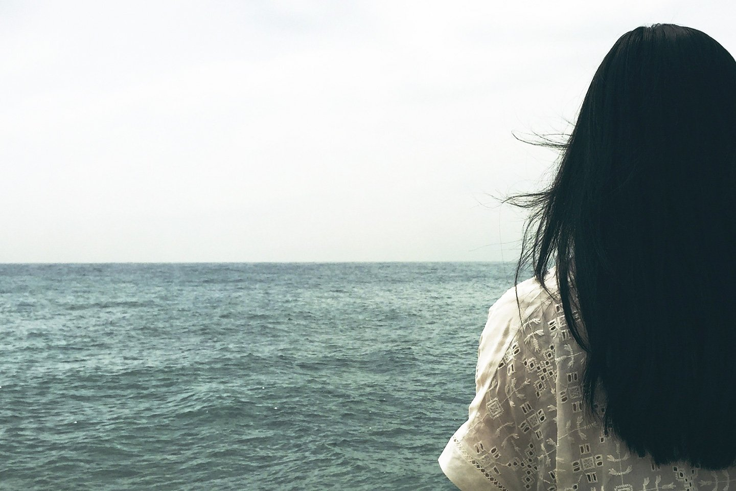 Woman with black hair is staring at the sea