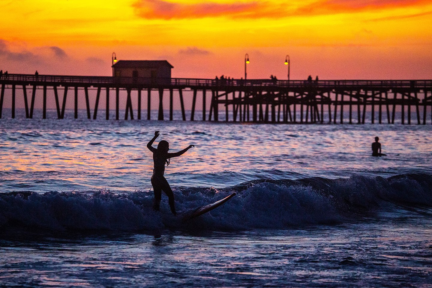 Surfers at t-street beach at sunset
