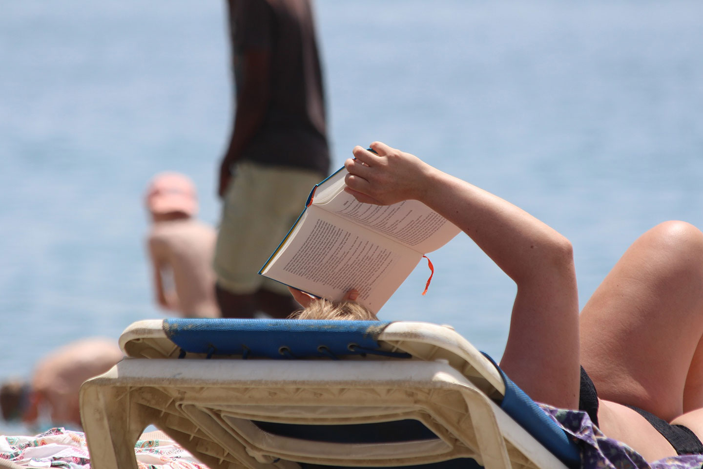 Lady reading book at the beach