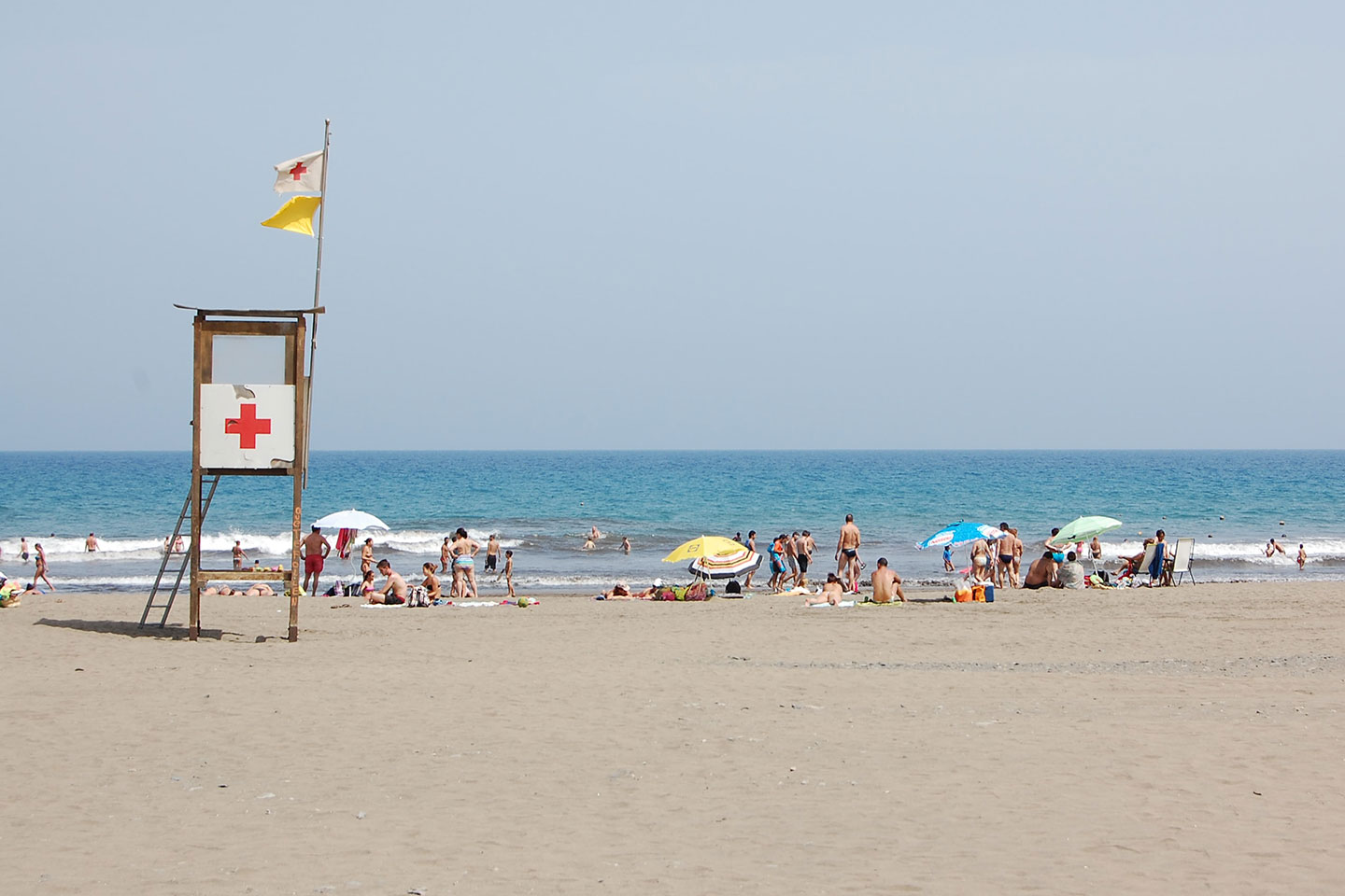 People at the beach near lifeguard tower