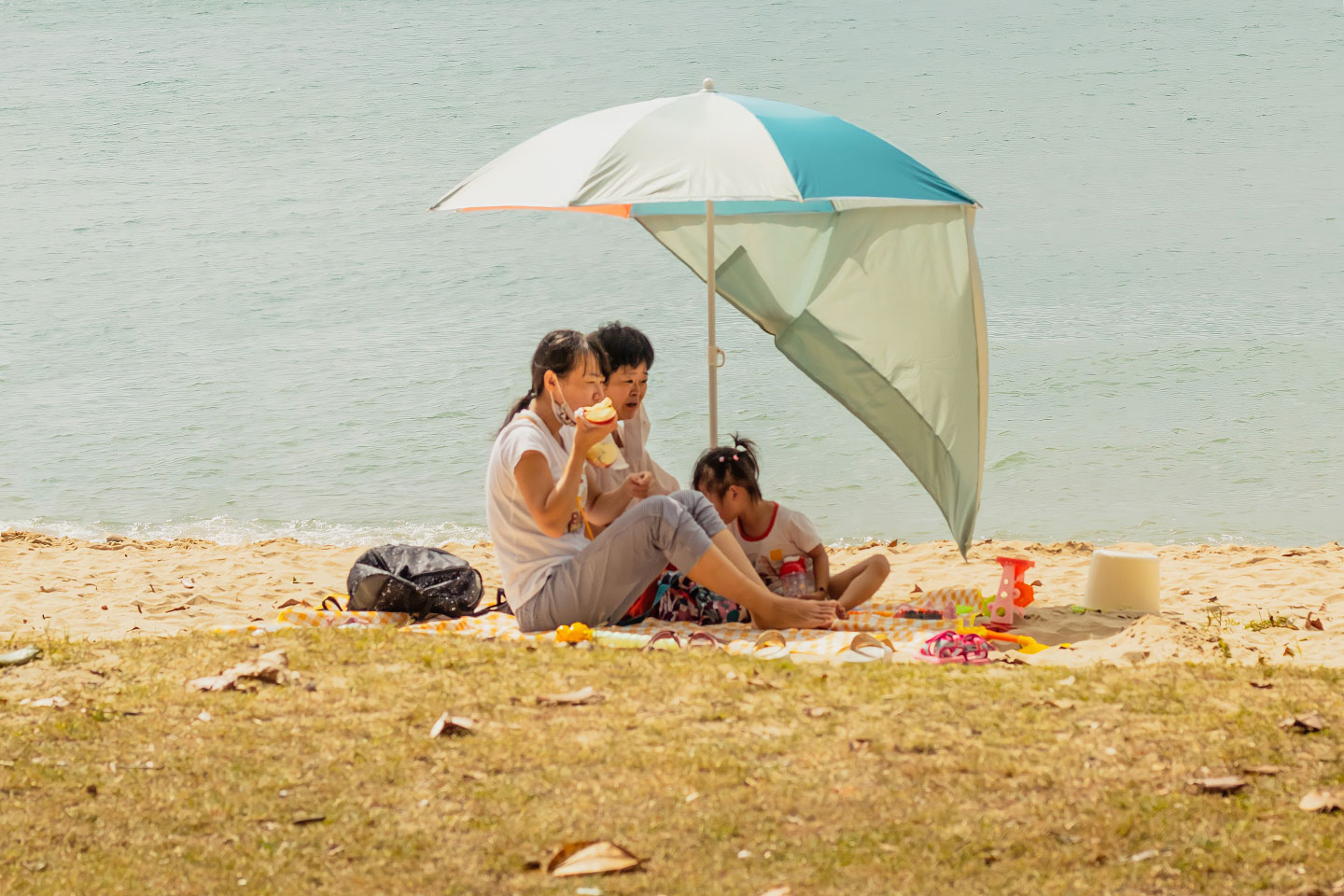 Family is eating under umbrella at the beach