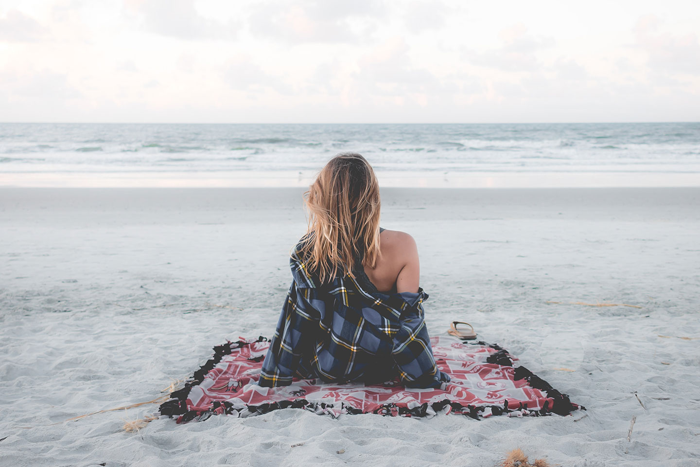 Lady is sitting on a pink blanket at the beach